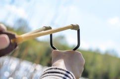 Jeune garçon visant le tir de bride au-dessus du lac Image libre de droits
