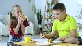 Jeune gar?on mangeant un hot-dog sur le fond d'une fille qui fait des exercices clips vidéos