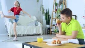 Jeune gar?on mangeant un hot-dog sur le fond d'une fille qui fait des exercices banque de vidéos
