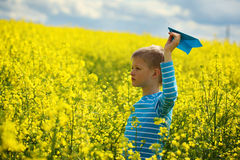 Jeune garçon avec l'avion de papier contre le ciel bleu et le champ jaune Flo Photo stock