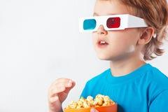 Jeune garçon blond en verres stéréo mangeant du maïs éclaté Images stock