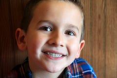 Jeune garçon de sourire avec de grands, noisette yeux Image stock