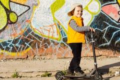 Jeune garçon de sourire posant sur son scooter Images stock
