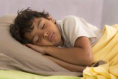 Jeune garçon dormant entièrement dans son lit Photographie stock libre de droits