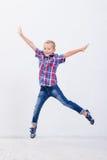 Jeune garçon heureux sautant sur le fond blanc Photo libre de droits