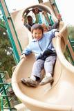 Jeune garçon jouant sur la glissière dans le terrain de jeu Photographie stock libre de droits