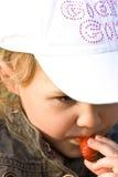 Jeune garçon mangeant du fruit dans le secret Photographie stock