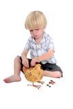 Jeune garçon mettant l'argent dans une tirelire Photo libre de droits