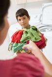 Jeune garçon retenant une pile de blanchisserie Images libres de droits