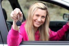 Jeune gestionnaire féminin de sourire affichant une clé image stock