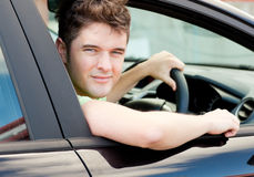 Jeune gestionnaire mâle heureux se reposant dans son véhicule photos stock