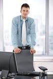Jeune gestionnaire restant dans le sourire de bureau image libre de droits