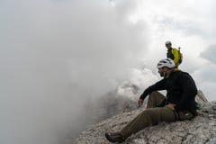Jeune grimpeur de montagne masculin sur une crête de montagne de dolomite appréciant la vue avec son guide se tenant derrière photo stock