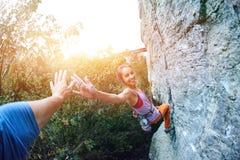 Jeune grimpeur de roche féminin mince s'élevant sur la falaise photos stock