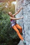 Jeune grimpeur de roche féminin mince s'élevant sur la falaise photos libres de droits