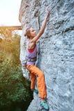 Jeune grimpeur de roche féminin mince s'élevant sur la falaise image stock