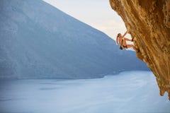 Jeune grimpeur de roche féminin sur l'itinéraire exaltant sur la falaise images stock