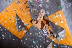 Jeune grimpeur de roche masculin dans le gymnase s'élevant d'intérieur photographie stock libre de droits