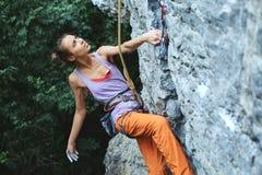 Jeune grimpeur de roche mince de femme s'élevant sur la falaise photo stock