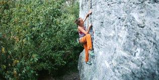 Jeune grimpeur de roche mince de femme s'élevant sur la falaise images libres de droits