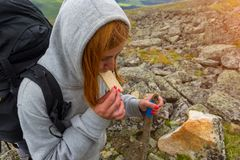 Jeune grimpeur roux de fille mangeant le casse-croûte pendant une montée vers le haut de images libres de droits