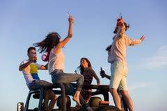 Jeune groupe ayant l'amusement sur la plage et dansant dans une voiture convertible Image stock