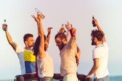 Jeune groupe ayant l'amusement sur la plage et dansant dans une voiture convertible Photo stock