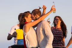 Jeune groupe ayant l'amusement sur la plage et dansant dans une voiture convertible Photos stock