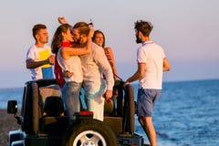 Jeune groupe ayant l'amusement sur la plage et dansant dans une voiture convertible Photos libres de droits