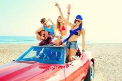 Jeune groupe ayant l'amusement sur la plage jouant la guitare Photographie stock libre de droits