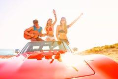 Jeune groupe ayant l'amusement sur la plage jouant la guitare Photos libres de droits