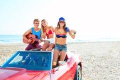 Jeune groupe ayant l'amusement sur la plage jouant la guitare Image libre de droits