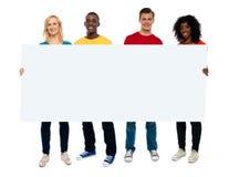 Jeune groupe confiant affichant l'affiche blanc Images stock