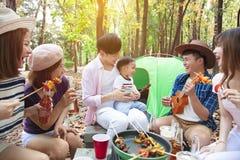 jeune groupe d'amis appr?ciant la partie et camper de pique-nique photos stock
