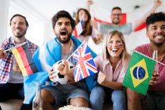 Jeune groupe d'amis observant le sport à la télévision Images libres de droits