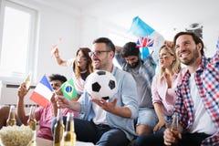 Jeune groupe d'amis observant le sport à la télévision Photo libre de droits