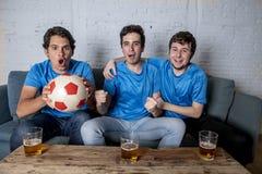 Jeune groupe d'hommes heureux et enthousiastes observant une partie de football sur le divan Photo libre de droits