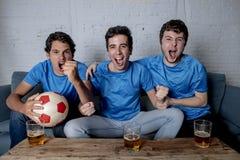 Jeune groupe d'hommes heureux et enthousiastes observant une partie de football sur le divan Photos stock