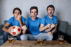 Jeune groupe d'hommes heureux et enthousiastes observant une partie de football sur le divan Photographie stock