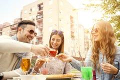 Jeune groupe de personnes riantes mangeant de la pizza et ayant l'amusement image stock