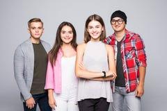 Jeune groupe de sourire heureux d'amis se tenant ensemble d'isolement sur le blanc Photos libres de droits