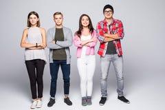 Jeune groupe de sourire heureux d'amis se tenant ensemble d'isolement sur le blanc Photographie stock libre de droits