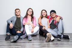 Jeune groupe de teengers d'étudiants d'amis se reposant sur le plancher Photo libre de droits