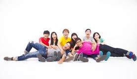 Jeune groupe heureux s'asseyant ensemble Photo libre de droits