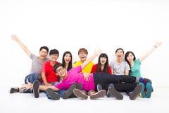 Jeune groupe heureux s'asseyant ensemble Images stock