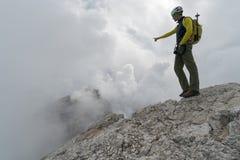 Jeune guide masculin de montagne sur une crête de montagne de dolomite indiquant le paysage photo stock