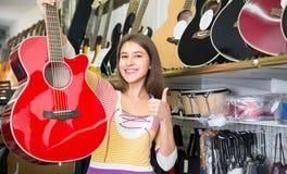 Jeune guitare choising femelle Photo stock