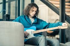 Jeune guitariste focalisé avec l'instrument de musique d'établissement de cheveux onduleux images libres de droits