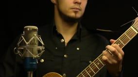 Jeune guitariste jouant sur la guitare acoustique banque de vidéos