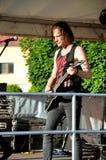 Jeune guitariste, membre de groupe de musique rock le paranoïde, support dans l'étape devant le microphone pendant le concert Image stock